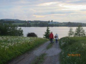 Kaksi henkilöä kävelee järveä kohti.