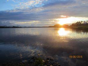 Järvimaisema, auringo paistaa kuvan oikealta puolelta.