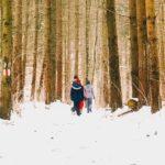 Ihmisiä kävelemässä lumisessa metsässä.