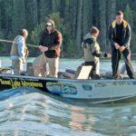 Neljä ihmistä kalastelemassa veneessä.