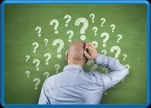 Henkilö kasvot liitutaulua kohti, liitutaulu täynnä kysymysmerkkejä