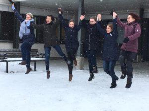 Ihmisjoukko hyppää ilmaan kädet yhdessä