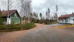 Kuvassa kaksi taloa. Talojen välistä menee autotie.
