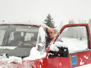 Kuvasssa vanha herra Ikaalisten logolla varustetun auton ulkopuolella talvimaisemassa