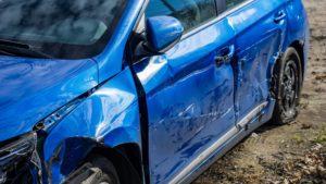 Kuvassa sininen auto, joka on täynnä lommoja.