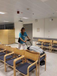Kuvassa siivooja puhdistamassa lattiaa puhdistuslaitteella