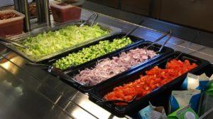 Kuvassa kouluruokalan salaattiastiat